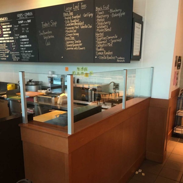 glass panels surrounding corner of cafe counter with black chalkboard menu on the wall