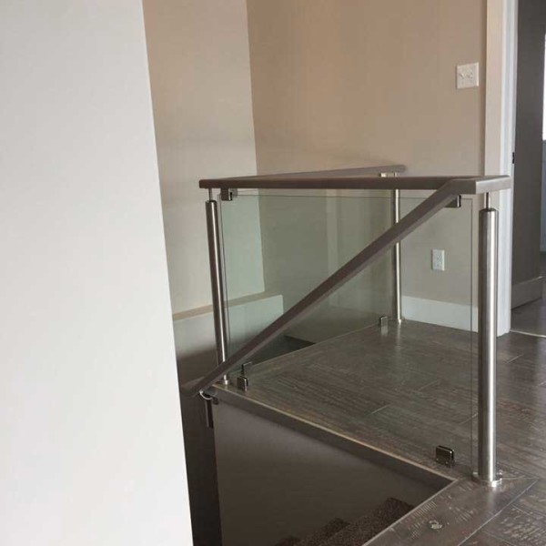 top of stairs with dark brown hardwood floors and glass and metal modern railings